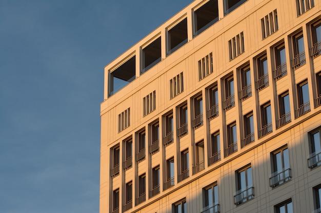 Edifício moderno com janelas sob um céu azul e luz do sol ao anoitecer