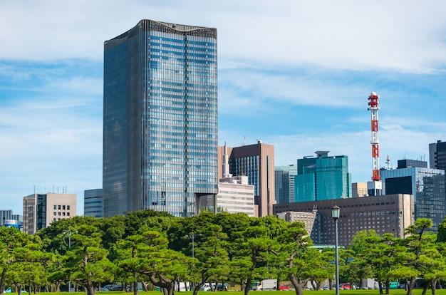 Edifício moderno com o jardim verde do zen no céu azul no tóquio, japão.