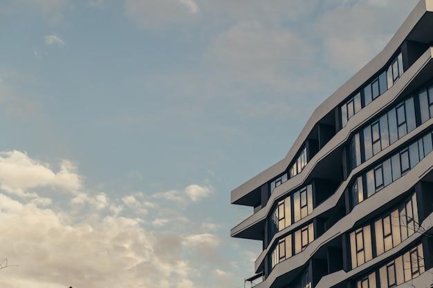 Edifício moderno de ângulo baixo com arranha-céu de nuvens