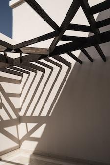 Edifício moderno de estilo oriental com paredes bege e sombras da luz solar do trilho.