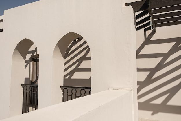 Edifício moderno de estilo oriental com paredes bege, janelas e sombras da luz do sol do trilho nas paredes
