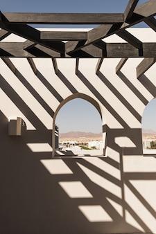 Edifício moderno de estilo oriental com paredes bege, janelas e sombras da luz do sol do trilho