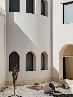 Edifício moderno de estilo oriental com paredes bege, janelas e sombras de luz solar