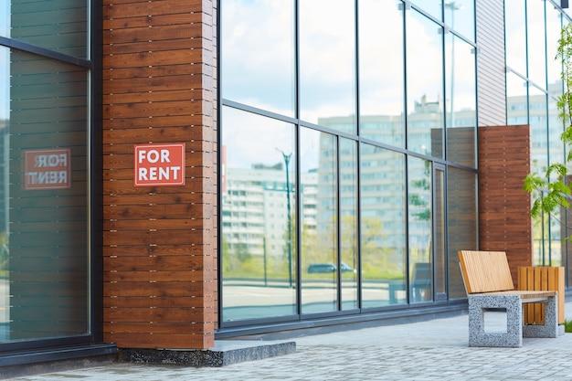 Edifício moderno de vidro com cartaz para alugar