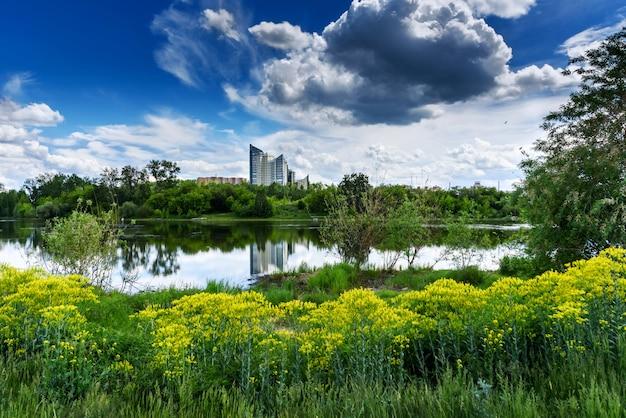 Edifício moderno é refletido no lago no parque da cidade. dia de sol de verão em uma cidade com belas nuvens