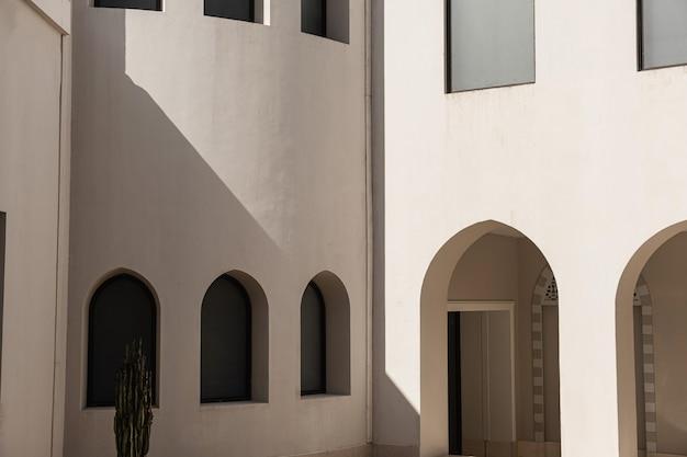 Edifício moderno em estilo oriental com janelas e sombras da luz do sol nas paredes bege