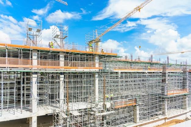 Edifício moderno está em construção, andaimes de metal e céu azul