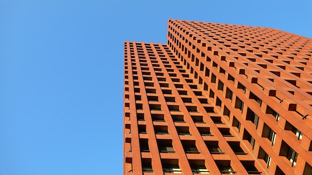 Edifício moderno no andar de cima vermelho e céu azul brilhante