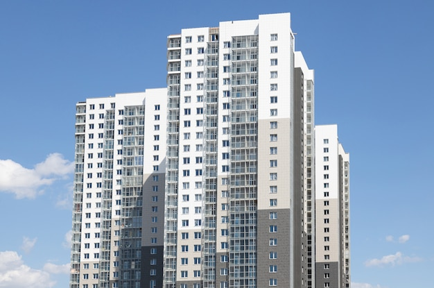 Edifício multi-familiar branco-cinza alto contra o céu azul