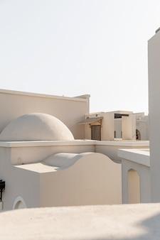 Edifício oriental moderno com paredes bege e céu azul.