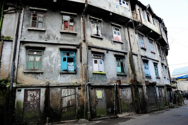 Edifício redondo sujo velho e úmido com muitas janelas e portas quebradas