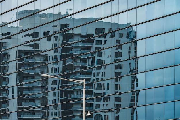 Edifício refletido em uma fachada de vidro