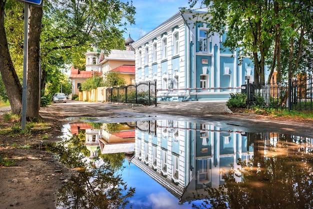 Edifício residencial com reflexo em uma poça em vologda em um dia ensolarado de verão. inscrição: casa residencial, final do século 18