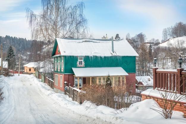 Edifício residencial de madeira na rua nikolskaya em plyos à luz de um dia de inverno sob um céu azul