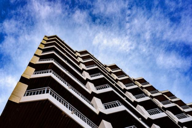 Edifício residencial de padrões arquitetônicos simétricos com fundo azul nuvens