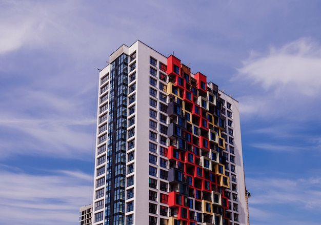 Edifício residencial moderno com uma fachada brilhante contra o céu azul. hipoteca e construção