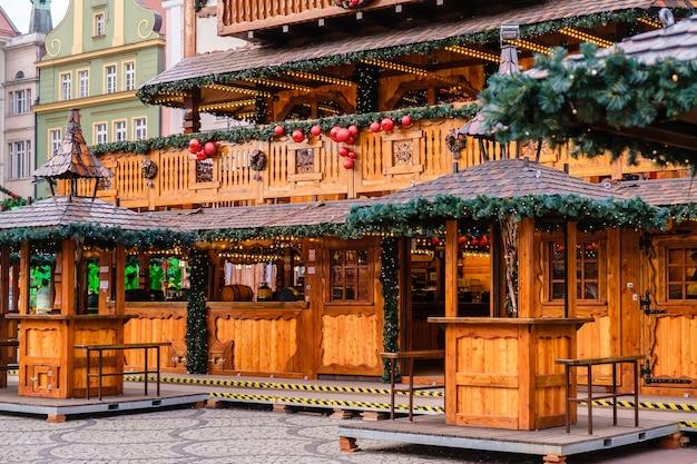 Edifício vintage de madeira decorado com guirlanda de iluminação e muitas bolas vermelhas de natal