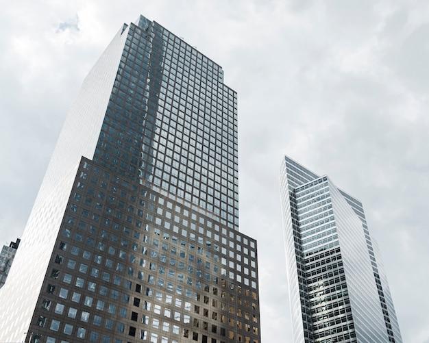 Edifícios altos de baixo ângulo com nuvens cinzentas