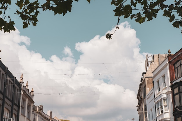 Edifícios antigos e os cabos de cabos sob as nuvens no céu