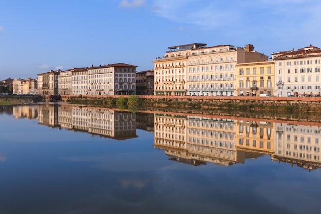 Edifícios antigos, refletindo no rio arno, em florença. casas w