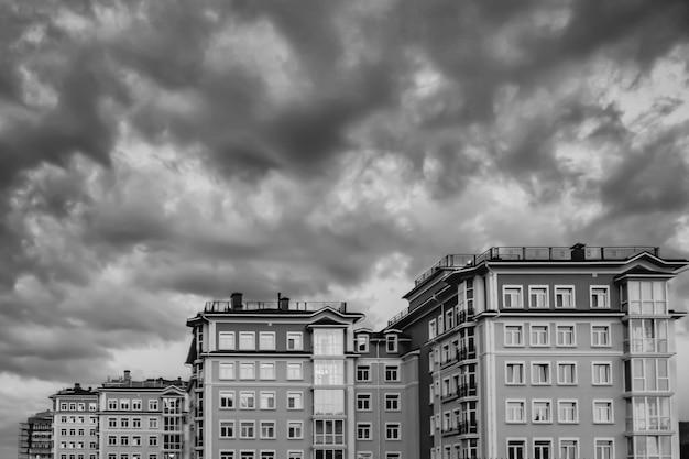 Edifícios ao pôr do sol à noite, sob um céu escuro dramático. krasnoyarsk, rússia. preto branco.