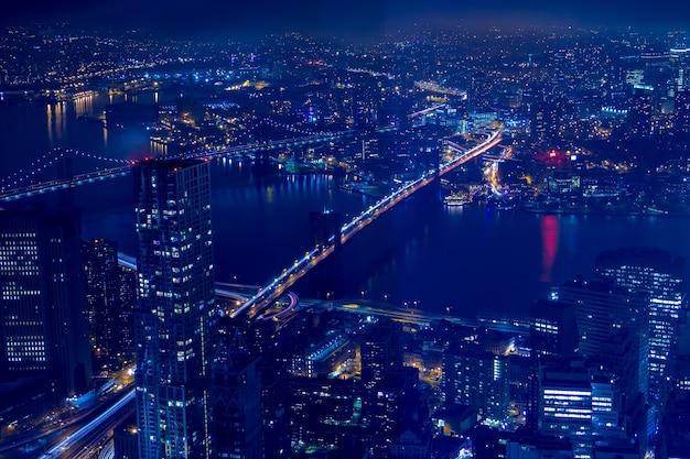 Edifícios, arranha-céus, ruas, as pontes de brooklyn e manhattan à noite na cidade de nova york. vista aérea
