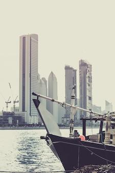 Edifícios de abu dhabi com o antigo barco de pesca na frente