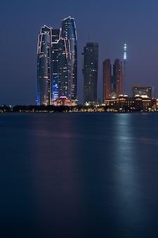 Edifícios de abu dhabi vistos do mar à noite