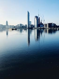 Edifícios de arranha-céus ao entardecer junto ao rio tamisa. reflexões na água.