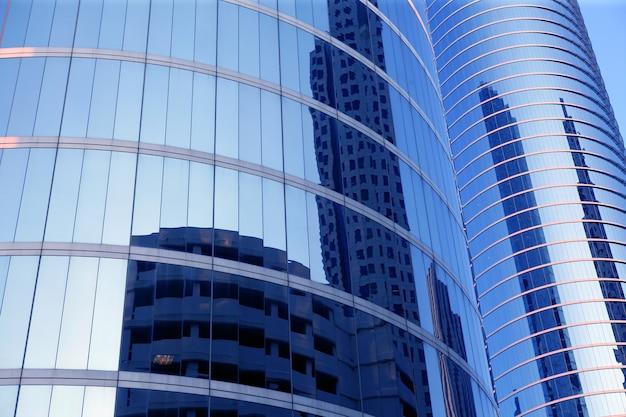 Edifícios de arranha-céus de fachada de vidro azul espelho