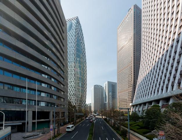 Edifícios de arranha-céus de tóquio e céu azul com rua em shinjuku, tóquio, japão