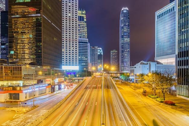 Edifícios do arranha-céus do escritório e tráfego ocupado na estrada da estrada com as trilhas claras borradas dos carros.