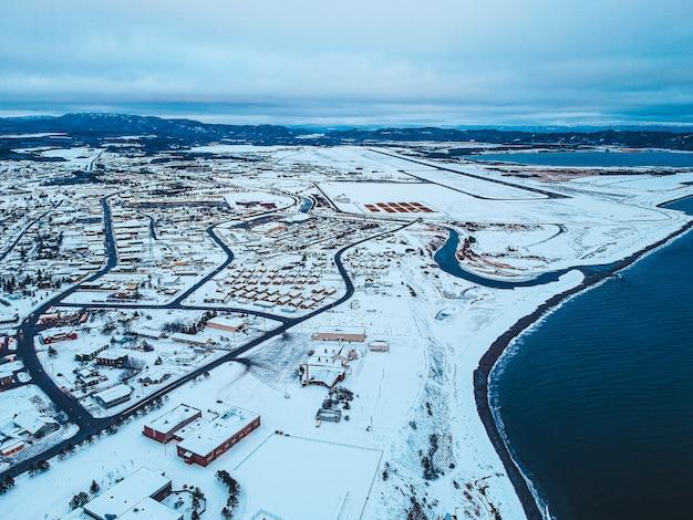 Edifícios e estradas em campo de neve durante o dia
