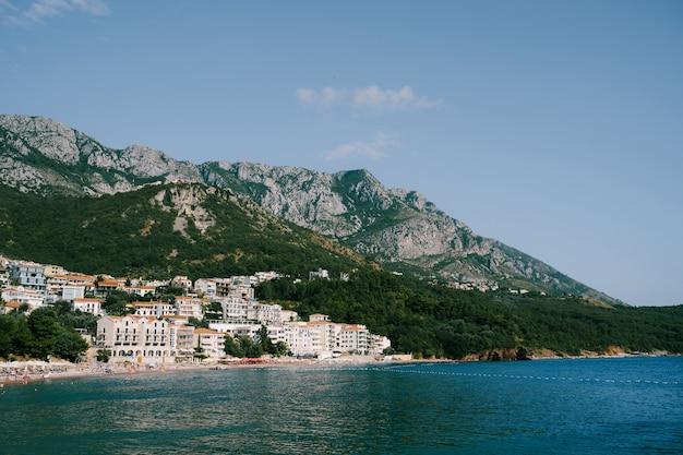 Edifícios e hotéis na costa montenegrina, tendo como pano de fundo as montanhas rochosas da vila