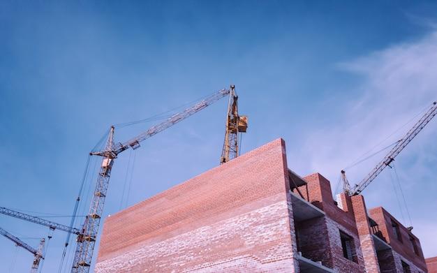 Edifícios residenciais em construção casa inacabada e guindaste de torre amarelo