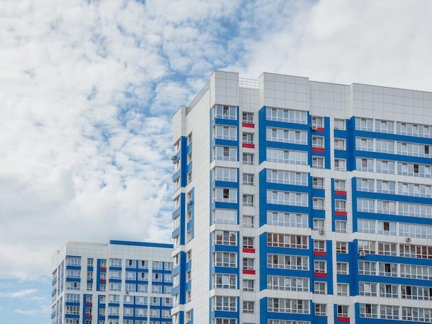 Edifícios residenciais novos, bonitos e modernos. parede colorida no fundo do céu azul. copie o espaço.