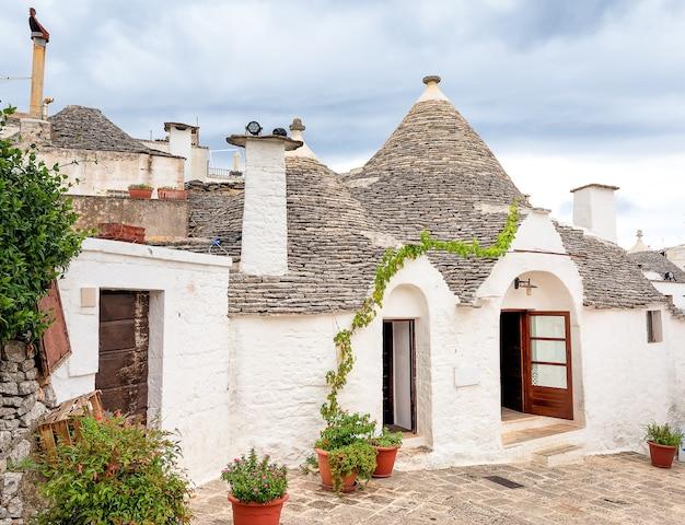 Edifícios trulli brancos, videira e flores. alberobello, apúlia, itália