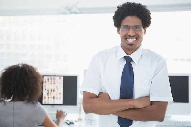 Editor considerável novo que sorri na câmera com o colega que trabalha atrás dele
