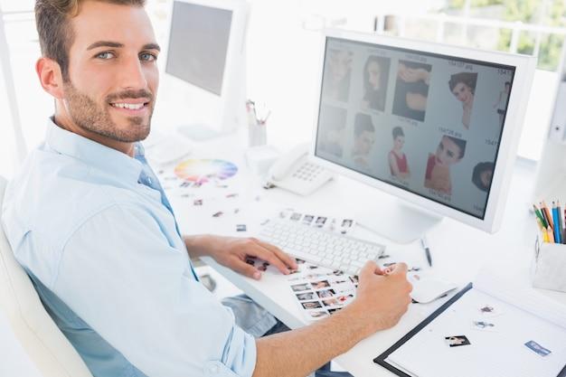 Editor de fotos masculinas trabalhando no computador em um escritório brilhante