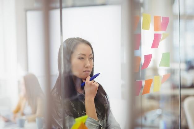 Editor de fotos pensativo olhando para notas adesivas coloridas em vidro