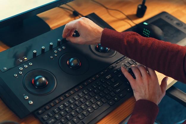 Editor de vídeo com as mãos ajustando a cor ou o som no console de trabalho m
