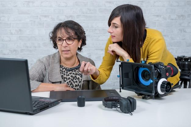 Editor de vídeo de mulher e jovem assistente usando tablet gráfico