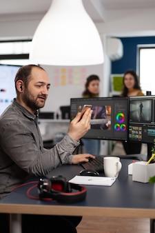 Editor de vídeo discutindo on-line com o designer do cliente segurando um smartphone