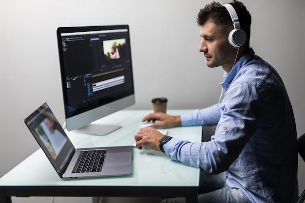 Editor de vídeo jovem que trabalha com filmagens em seu computador pessoal com grande tela em um escritório moderno