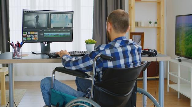 Editor de vídeo profissional em cadeira de rodas devido à deficiência motora.