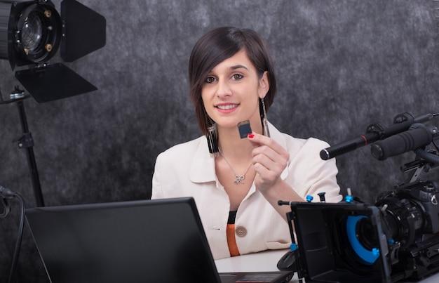 Editor de vídeo sorridente jovem mostrando um cartão sd
