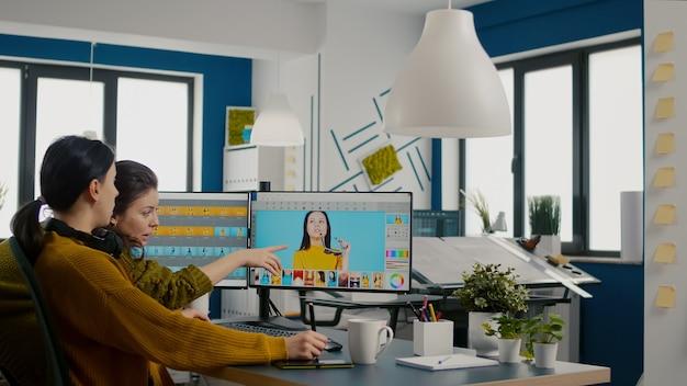 Editores de fotos de mulheres confiantes sentados em um local de trabalho criativo retocando fotos, o diretor de arte verificando a técnica de criação de cores conversando com um trabalhador