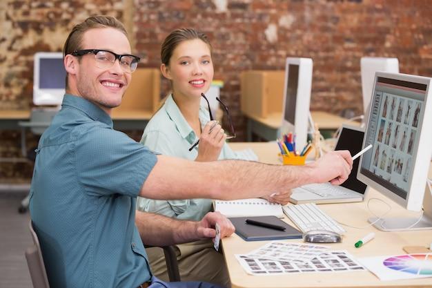 Editores de fotos ocasionais usando o computador no escritório