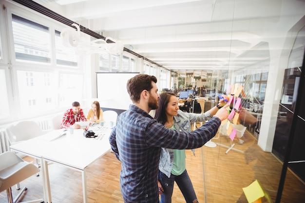 Editores de fotos que olham notas pegajosas no vidro na sala de reuniões