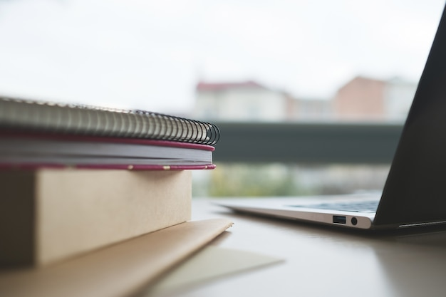 Educação à distância livros blocos de notas e laptop sobre a mesa e mão de homem segurando dinheiro